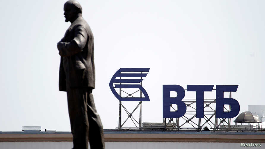FILE PHOTO: A sign for the logo of VTB Bank on the top of a building is pictured behind a monument of Soviet state founder Vladimir Lenin in Stavropol, Russia, July 17, 2014.