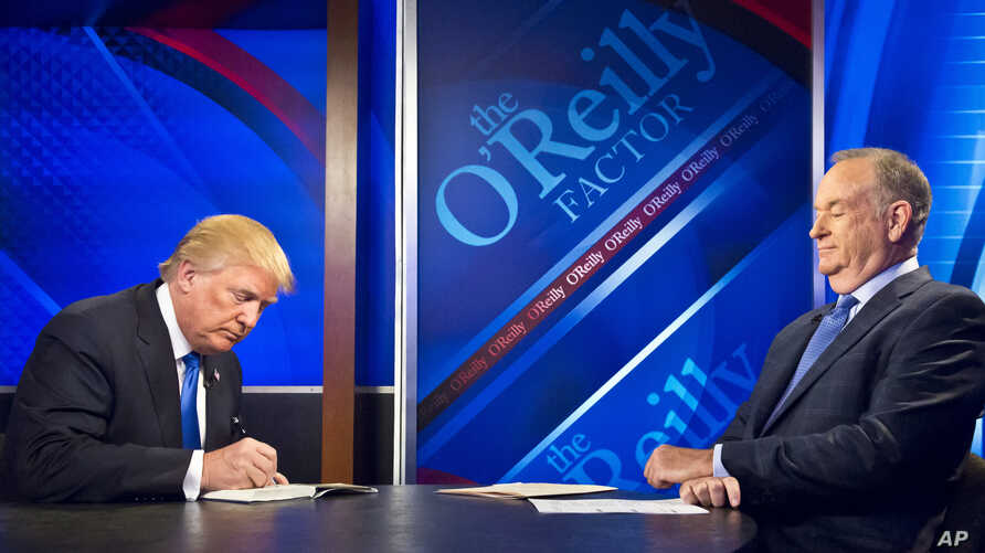 "Republican presidential candidate Donald Trump, left, signs his book for Bill O'Reilly, right, during his appearance on Fox's news talk show ""The O'Reilly Factor,"" Nov. 6, 2015, in New York."