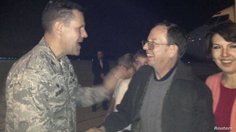 Jeffrey Fowle and his wife, Tatyana, are greeted by U.S. Air Force Col. John Devillier upon arrival at Wright-Patterson Air Force Base in Ohio after his release in North Korea, Oct. 22, 2014.
