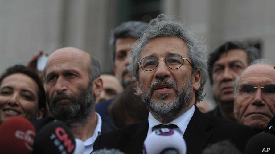 Can Dundar, the editor-in-chief of opposition newspaper Cumhuriyet, right, and Erdem Gul, left, the paper's Ankara representative, speak to the media after their trial in Istanbul, March 25, 2016.