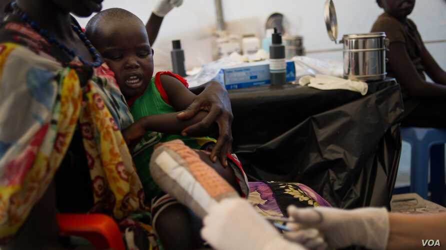 A boy who suffered severe burns to his leg is tended to by a Médecins Sans Frontières (MSF) doctor at the MSF clinic set up at the camp for  displaced people in the grounds of the United Nations Mission to South Sudan (UNMISS) base in Juba, South Sud