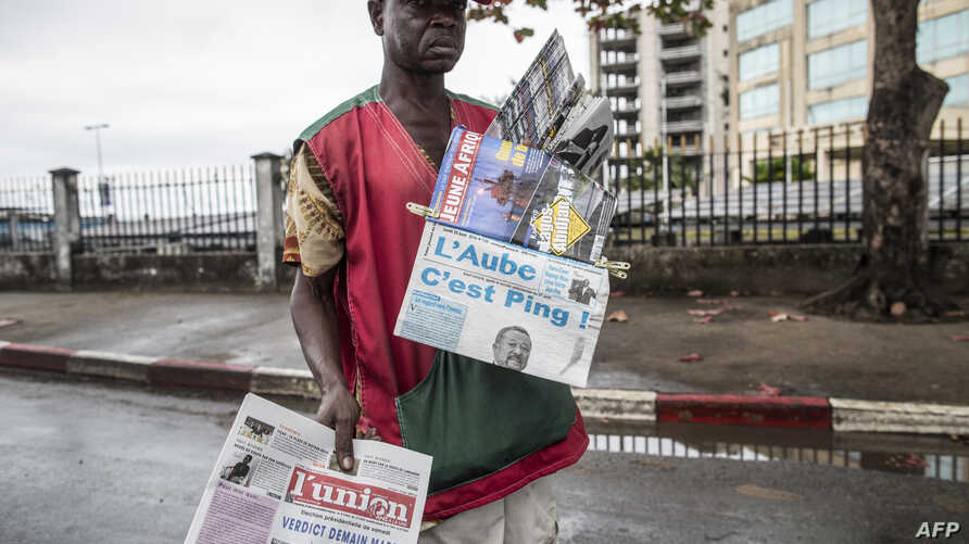 A newspaper vendor looks for customers at a street light in Libreville on Aug. 29, 2016 while displaying local papers reporting on the outcome of Gabons's presidential elections.