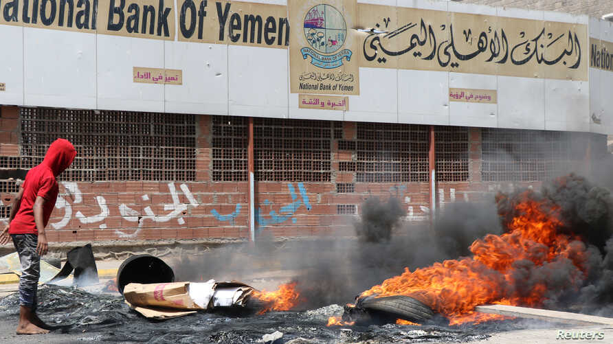 Protesters block a street with burning tires after the Yemeni rial plunged against foreign currencies, in Aden, Yemen, Sept. 2, 2018.