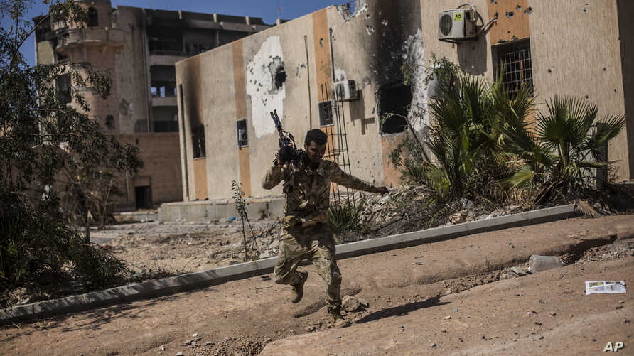 FILE - A fighter of the Libyan forces, affiliated with the Tripoli government, runs for cover while fighting against Islamic State positions in Sirte, Libya, Sept. 22, 2016. IS forces have since been dispersed, yet they can thrive in porous security