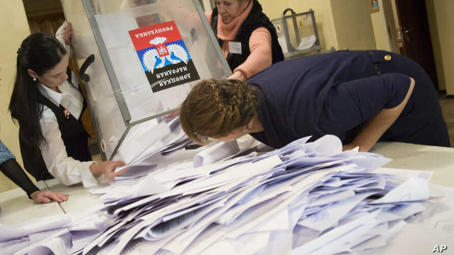 Election officials empty a ballot box during rebel elections at a polling station in the city of Donetsk, eastern Ukraine, Nov. 2, 2014.
