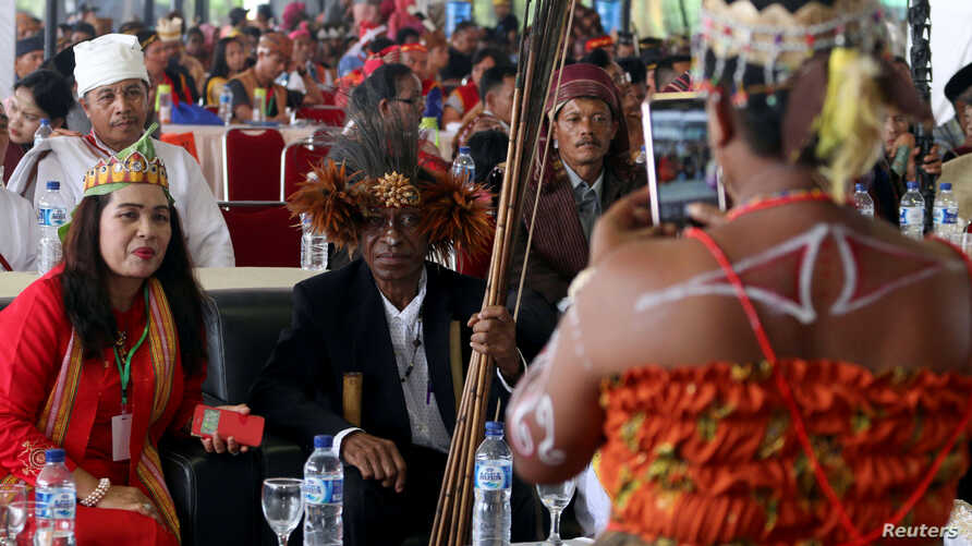 Participants take photos on the sidelines of an indigenous peoples gathering, near Medan, Sumatra Island, Indonesia, March 17, 2017.