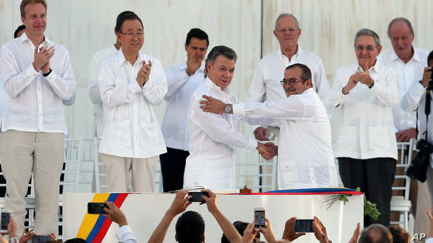 Colombia's President Juan Manuel Santos, front left, and the top commander of the Revolutionary Armed Forces of Colombia (FARC) Rodrigo Londono, known by the alias Timochenko, shake hands after signing the peace agreement between Colombia's governmen