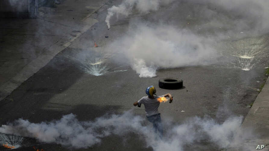 A demonstrator throws a fire bomb at security forces launching tear gas at an anti-government protest demanding Venezuelan President Nicolas Maduro open a so-called humanitarian corridor for the delivery of medicine and food aid, in Caracas, Venezuel