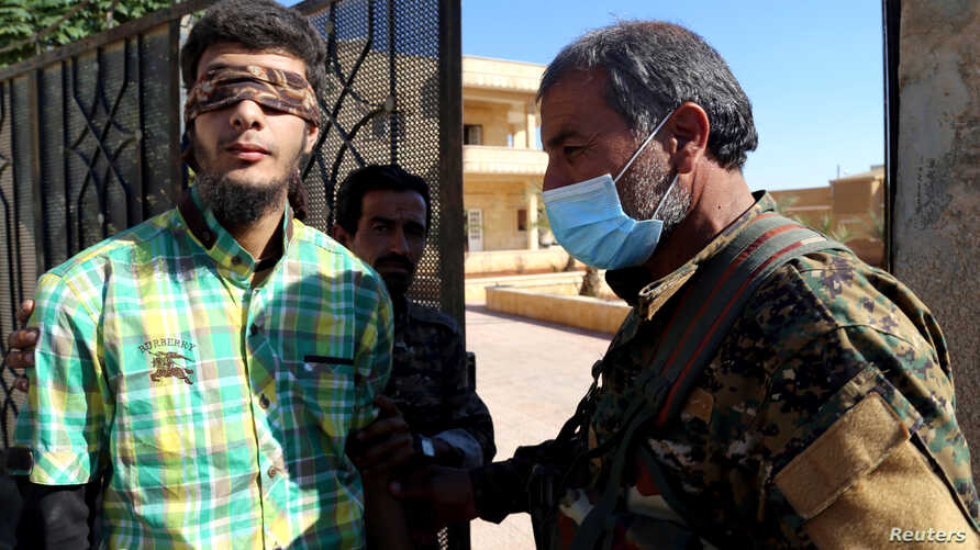 FILE - Members of the Syrian Democratic Forces escort a blindfolded civilian detainee suspected of being an Islamic State militant in Raqqa, Syria, Oct. 12, 2017.