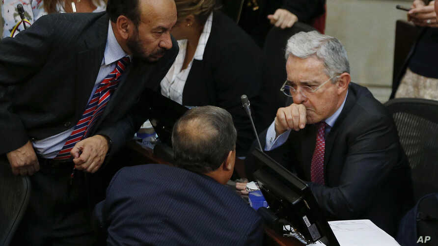 Former President Alvaro Uribe, right, talks to Senator of the Democratic Center Alfredo Rangel during a Senate session in Bogota, Colombia, Monday, Oct. 3, 2016. Colombians rejected a peace deal with leftist rebels in a national referendum Sunday. Ur