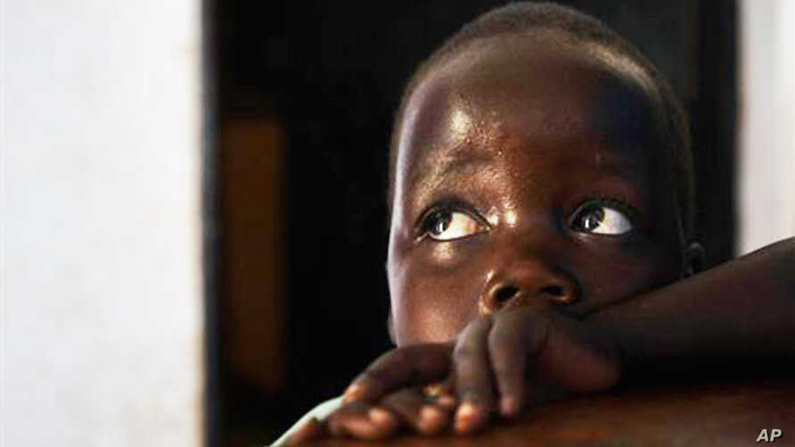"""In this photo taken Friday, April 27, 2012, in Gulu, Uganda, Betty, 3, looks up at her mother Adye Sunday, 25, unseen, who was abducted when she was 13 by Lord's Resistance Army leader Joseph Kony and forced to be one of his dozens of """"wives."""" She sa"""