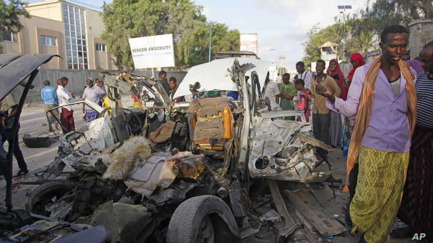 Somalis gather near the wreckage of a car used in an attack outside a beachfront restaurant in Mogadishu, Somalia, Aug. 26, 2016. Experts call for a unified counterterrorism effort.