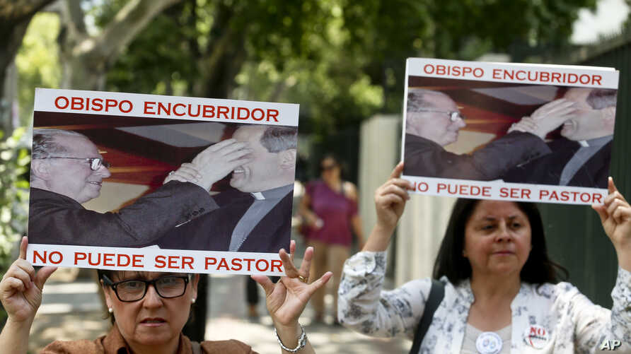 """FILE - Members of the movement Laity of Osorno hold up images showing the Rev. Fernando Karadima (L), and his protege Juan Barros, bishop of Osorno, with a message that reads in Spanish: """"A bishop who covers up cannot be a priest,"""" during a protest i"""