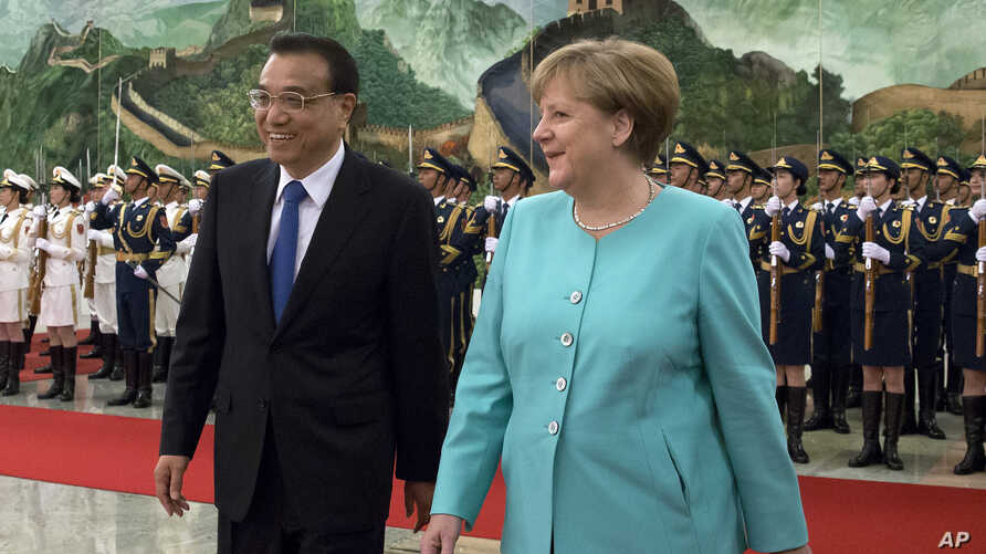 Germany's Chancellor Angela Merkel, right, chats with China's Premier Li Keqiang during a welcome ceremony at the Great Hall of the People in Beijing, Monday, June 13, 2016.