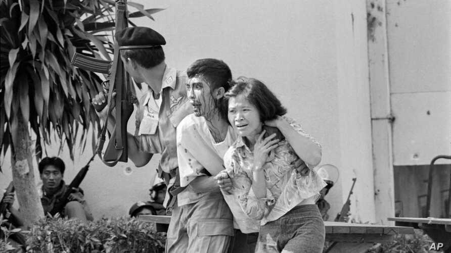 FILE - In this Oct. 6, 1976 file photo blood streaming down his face, a leftist student, center, wounded and captured by police is helped to an ambulance at the Thammasat University campus in Bangkok, Thailand.