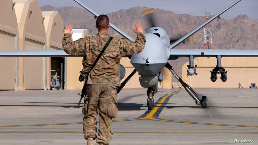A U.S. airman guides a U.S. Air Force MQ-9 Reaper drone as it taxis to the runway at Kandahar Airfield, Afghanistan March 9, 2016.