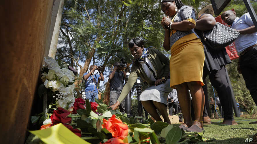 People lay flowers in honor of the dead outside the gate of the dusitD2 hotel complex which was attacked last week, at a wreath-laying event organized by the hotel complex management in Nairobi, Kenya, Jan. 22, 2019.