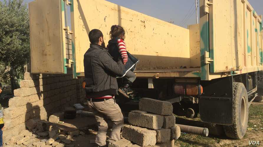 A father loads his child into an army truck to go to an internally displaced persons' camp in the Mosul suburbs, Iraq, Nov. 12, 2016. (H.Murdock/VOA)