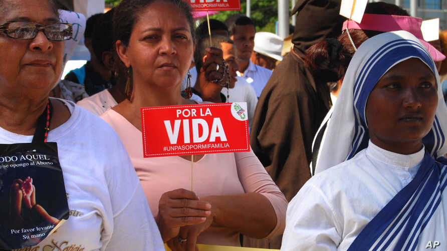 """FILE - Roman Catholics protest the legalization of abortion, bearing signs that read """"For life"""" outside Congress in Santo Domingo, Dominican Republic, Dec. 9, 2014. This week, after pressure from church groups, the country's high court reinstated a b"""