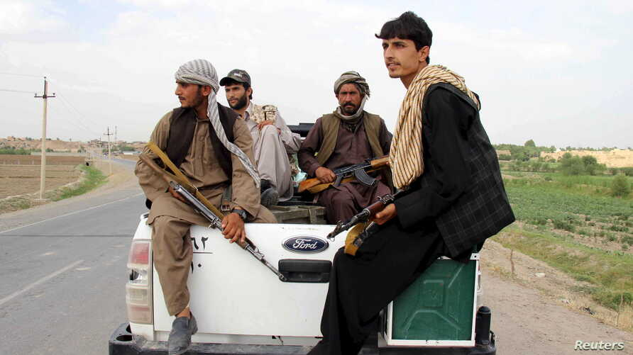 Afghan local police (ALP) sitting at the back of a truck drive past a checkpoint at Chardara district, in Kunduz province, Afghanistan, June 23, 2015.