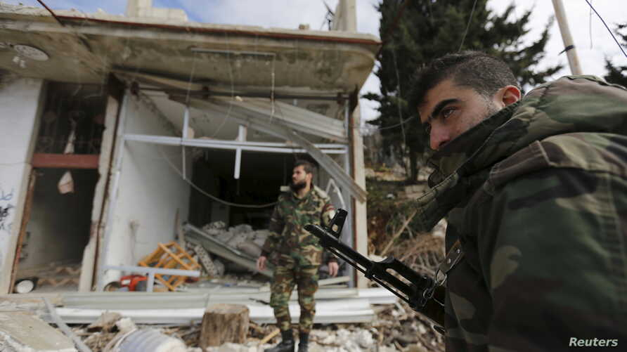 Forces loyal to Syria's President Bashar al-Assad stand in front of damaged shops in the town of Rabiya after they recaptured the rebel-held town in coastal Latakia province, Syria, Jan. 27, 2016.