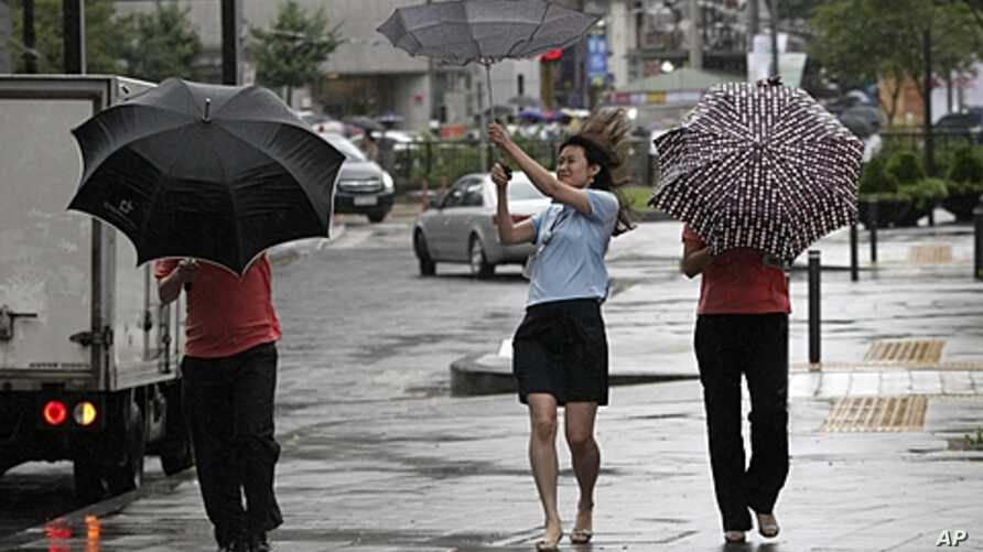 Passers-by try to manage their umbrellas in rain and strong wind generated by tropical storm Muifa in downtown Seoul, South Korea, Aug. 8, 2011.