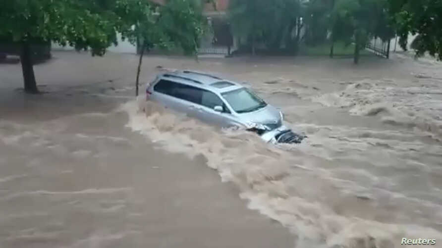 A vehicle sits in flowing floodwater in Culiacan, Sinaloa State, Mexico, Sept. 20, 2018, in this image obtained from social media video.