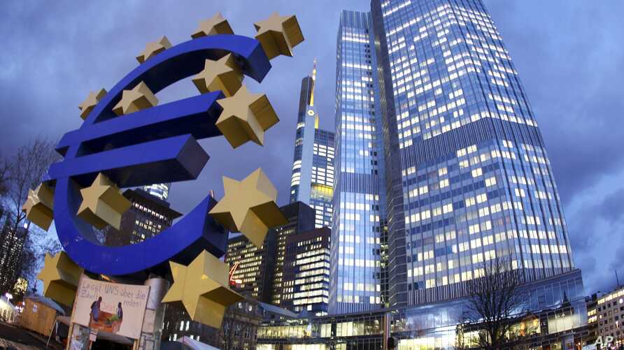 FILE - The Euro sculpture stands in front of the European Central Bank, right,  in Frankfurt, Germany.
