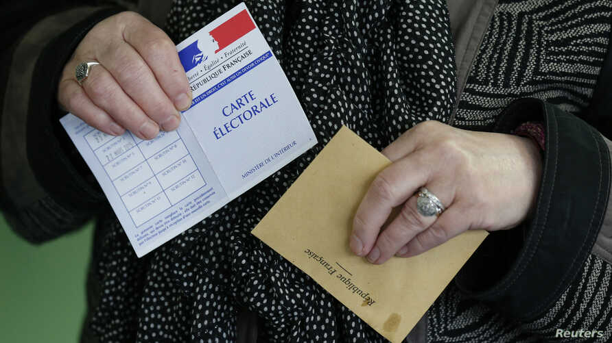 A woman prepares to cast her ballot at a polling station in Henin-Beaumont, northern France, March 29, 2015. France goes to the polls in a two-round departmental election for local officials on March 22 and March 29.