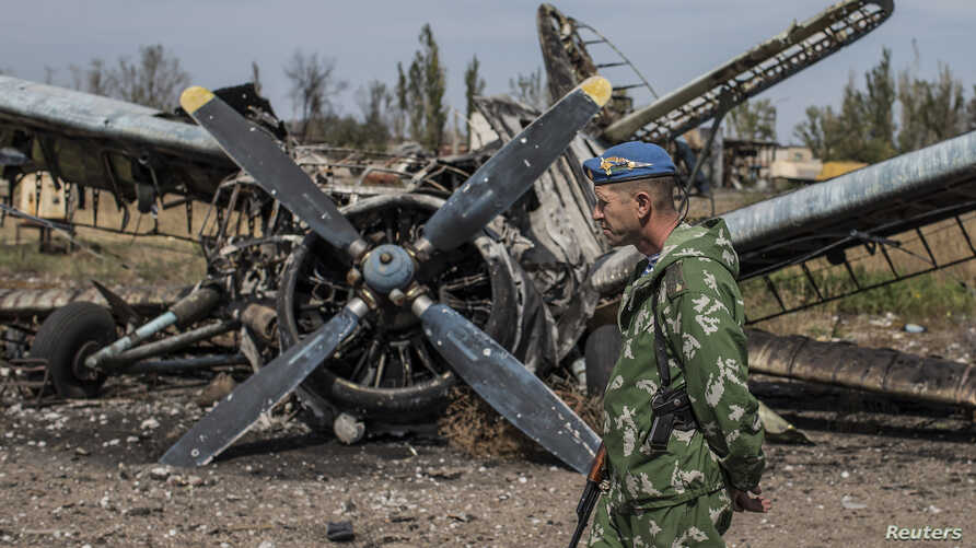 A pro-Russian rebel walks by a burnt-out plane at the destroyed airport in Luhansk, eastern Ukraine, Sept. 14, 2014.