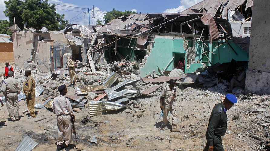 Somali soldiers look at the destroyed houses amidst the wreckage of a car bomb blast in Mogadishu, Somalia, May 17, 2017. Three bomb disposal experts were killed as they were trying to dismantle the car laden with explosives, according to police.