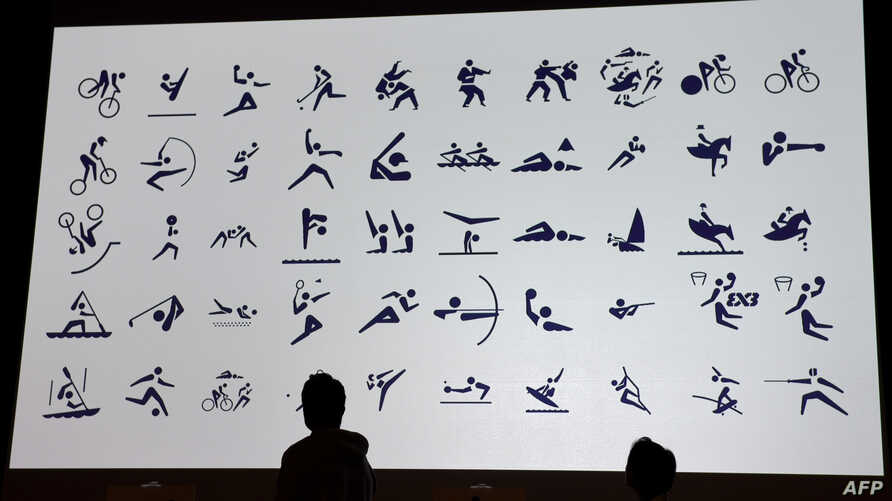 Japan's 4x100 metre relay Rio 2016 silver medallist Shota Iizuka (L) and national karate team member Kiyo Shimizu (R) look at a monitor displaying sports pictograms for the Tokyo 2020 Olympic Games during an unveiling ceremony in Tokyo, March 12, 201