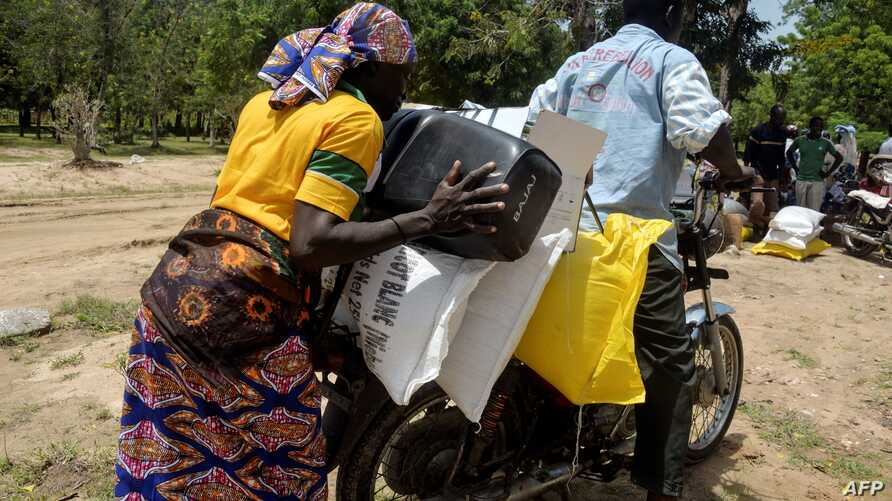 FILE - A Cameroonian displaced woman is seen loading her donated food onto a motorcycle outside a distribution center in Koza, in the extreme northern province, west of the Nigerian border, Sept. 14, 2016