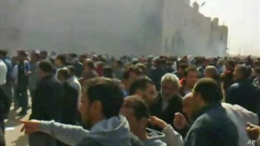 A crowd gathers as smoke billows from a building purported to be the internal security headquarters in Libya's second city of Benghazi in this video still grab, February 20, 2011