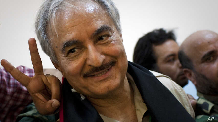 FILE - In this Friday, March 18, 2011 file photo, then Libyan senior Rebel commander Khalifa Hifter leaves a press conference in the court house in the center of Benghazi, eastern Libya.