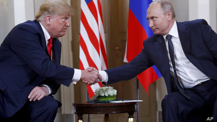 FILE - In this Monday, July 16, 2018, file photo, U.S. President Donald Trump, left, and Russian President Vladimir Putin shake hands at the beginning of a meeting at the Presidential Palace in Helsinki, Finland.