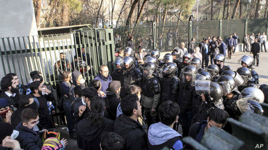 In this photo taken by an individual not employed by the Associated Press and obtained by the AP outside Iran, anti-riot Iranian police prevent university students to join other protesters over Iran weak economy, in Tehran, Iran, Saturday, Dec. 30, 2...