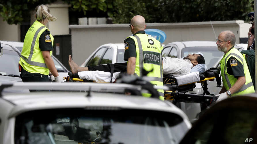 Ambulance staff take a man from outside a mosque in central Christchurch, New Zealand, March 15, 2019. A witness says many people have been killed in a mass shooting at a mosque in the New Zealand city of Christchurch.