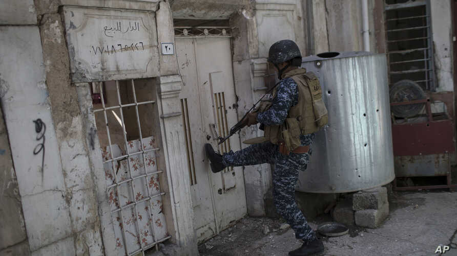 A federal policeman kicks open the door of a house to inspect the interior as fighting against Islamic State militants continues on the western side of Mosul, Iraq, March 29, 2017.