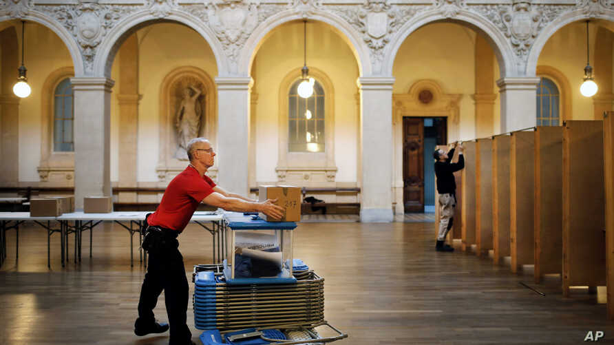 Workers prepare booths at a polling station in Lyon, central France, April 22, 2017. The first of two rounds of voting in France proper will take place on April 23.