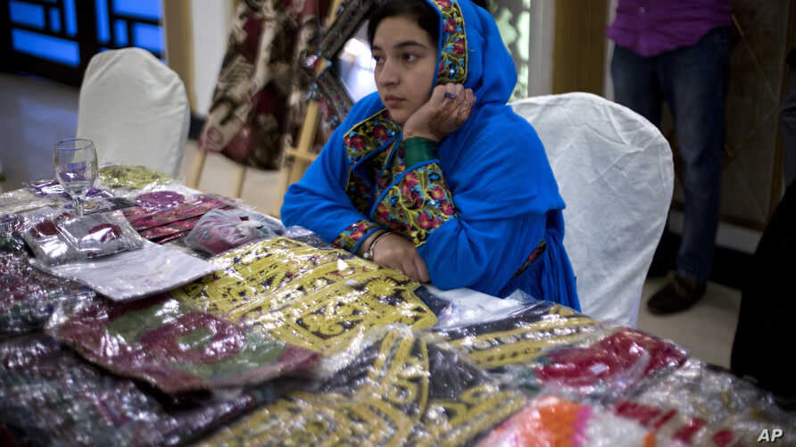 A refugee from neighboring Afghanistan, who fled her village with family due to war and famine, sells Afghan dresses at a reception organized by the United Nations High Commission for Refugees (UNHCR) on the occasion of the World Refugee Day in Islam