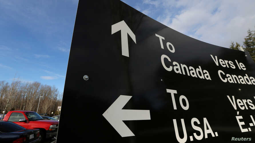 FILE - A sign giving directions is seen in the parking lot of the United States-Canada border in Surrey, British Columbia,  Feb. 16, 2017.
