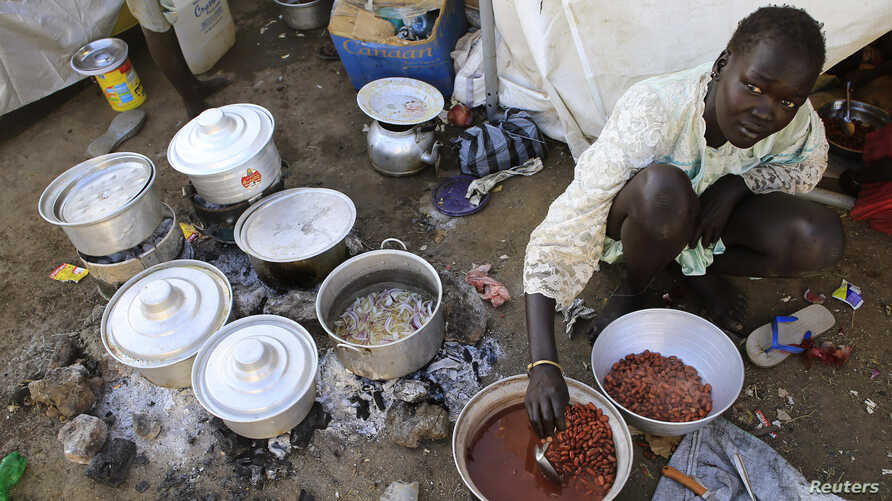 A displaced woman prepares a meal at Tomping United Nations base near Juba international airport, Dec. 24, 2013.