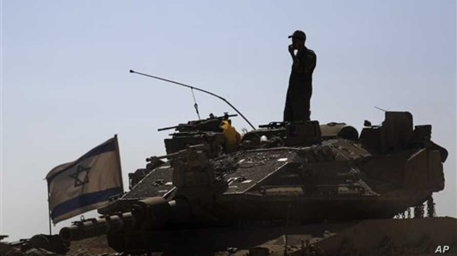 An Israeli soldier on a tank in a staging area near the Israel-Gaza border, Aug. 2, 2014.