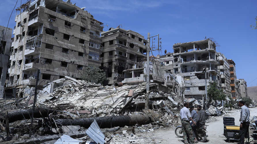 FILE - In this April 16, 2018, file photo, people stand in front of damaged buildings, in the town of Douma, the site of a suspected chemical weapons attack, near Damascus, Syria.