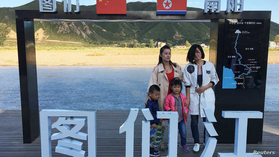 Tourists pose at the border with North Korea in Tumen, China, Aug. 30, 2017. China reported seven months of falling imports from North Korea.