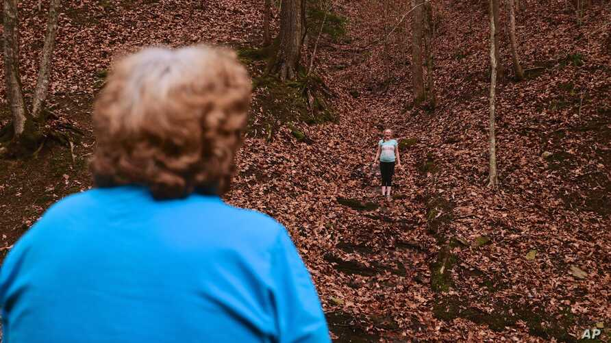 Maggie Hill, 67, watches Charity play in Madison, W.Va., on Thursday, Nov. 29, 2018. Hill adopted the 10-year-old girl about five years ago. Hill's son had been raising her but lost custody during his ongoing struggle with drug addiction, Hill said.