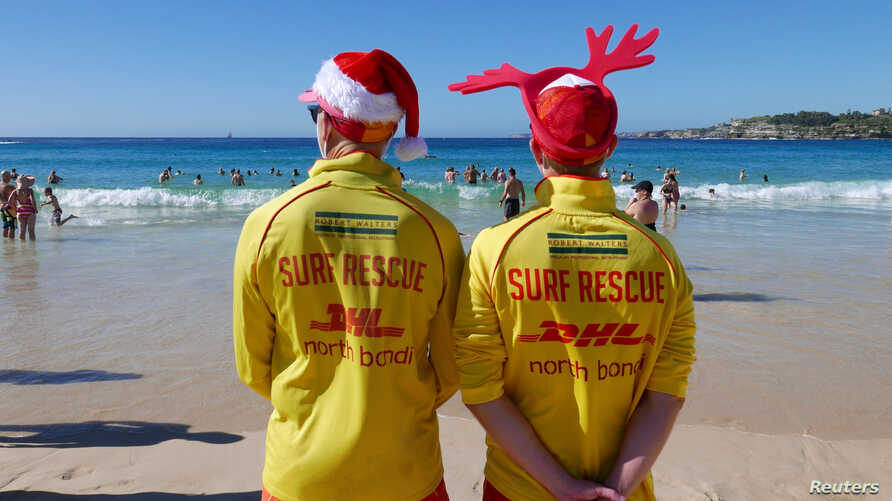 Simon, left, and Victor volunteer life guards from North Bondi Surf Life Saving Club, keep an eye on swimmers enjoying Christmas day on Bondi Beach, Sydney, Dec. 25, 2018. Australia looks set to sweat through one of its hottest Decembers ever.