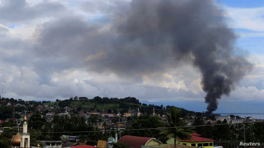 A black smoke comes from a burning building at a Marinaot town, after government troops' continuous assault with insurgents who have taken over large parts of the city, in Marawi City, southern Philippines, May 26, 2017.
