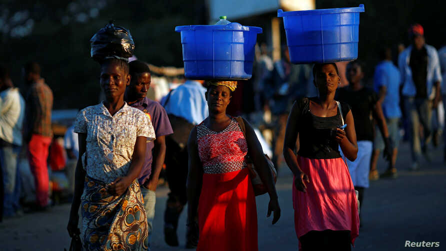 FILE - Women carry baskets with food items on their heads at a market in Blantyre, Malawi, July 10, 2017.